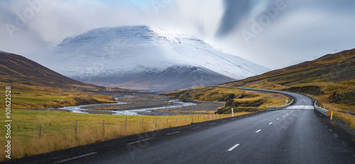 Leinwand Poster  Curve line road surround by yellow field with snow mountain background Autumn se