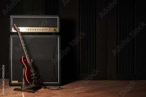 Photo Red electric guitar and classic amplifier on a dark background