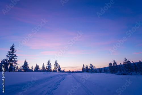 Foto op Aluminium Blauw Winter Evening Landscape with road and sunset