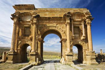 Algeria. Timgad (ancient Thamugadi). Paving stones of Decumanus Maximus street and 12 m high triumphal arch, called Trajan's Arch