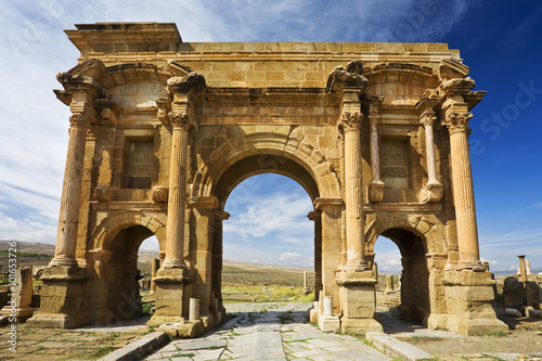 In de dag Algerije Algeria. Timgad (ancient Thamugadi). Paving stones of Decumanus Maximus street and 12 m high triumphal arch, called Trajan's Arch