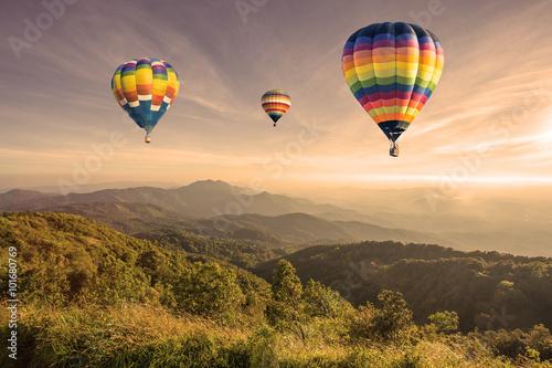 Poster Montgolfière / Dirigeable Hot air balloon above high mountain at sunset