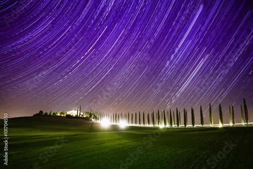 Photo Stands Violet Beautiful Tuscany night landscape with star trails on the sky, cypresses and shining road in green meadow. Natural outdoor amazing fantasy background.