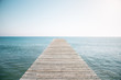 Wooden pier in the ocean with blue sky