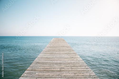 Wooden pier in the ocean with blue sky Wallpaper Mural