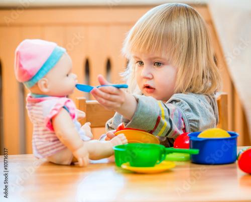 Photo girl feeding a doll