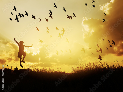 Photo  Happy child jumping with birds in sunset sky.