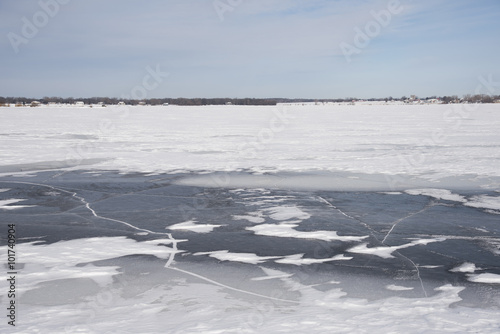 Photo  Dark, cracked ice has been exposed after the wind blew snow clear of frozen lake