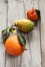 Arancia, Limone E Mandarino Appoggiati In Diagonale Su Asse Di Legno