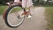 Девушка с длинными волосами в платье едет на велосипеде в парке