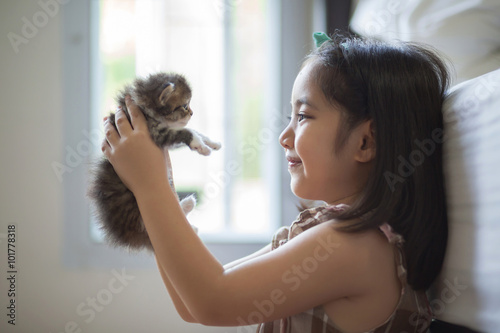 Photo  Adorable little asian girl kissing her kitten