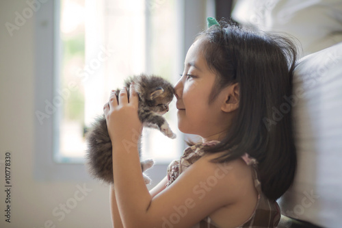 Adorable little asian girl kissing her kitten Canvas Print