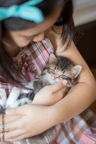 Photo  Adorable little asian girl giving her kitten a hug