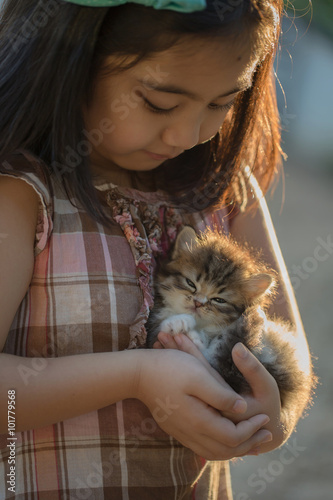 Photo  Adorable little asian girl giving her kitten a hug