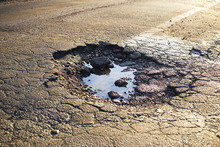 A Road Damaged By Rain And Snow, That Is In Need Of Maintenance. Broken Asphalt Pavement Resulting In A Pothole, Dangerous To Vehicles.