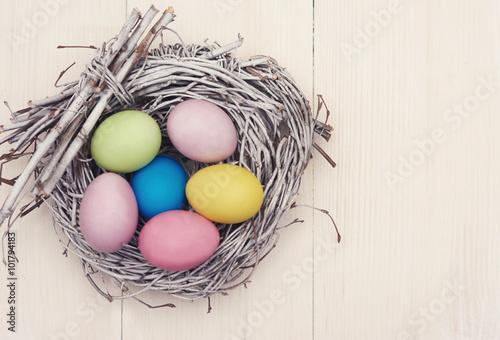 Wicker nest full of multi colored eggs. - 101794183