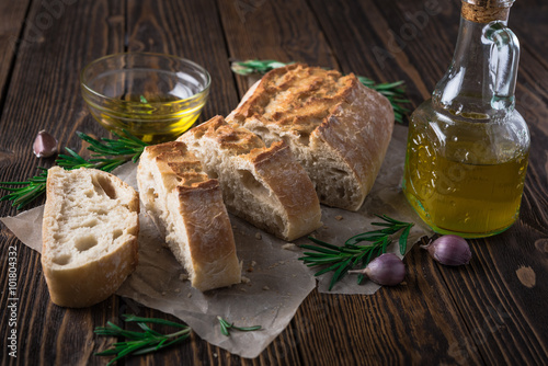 Sliced italian bread Ciabatta with rosemary on wooden background Poster