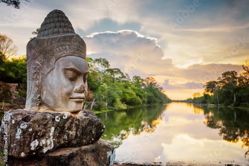 Photo Stone face Asura and sunset over moat. Angkor Thom, Cambodia