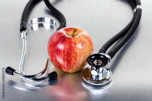 Fotografering  Fresh red apple and stethoscope on stainless steel