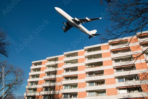 Fotografia, Obraz  Fluglärm, Flugzeug über Wohnhaus