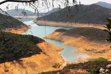 Hong Kong High Island Water Reservoir Running Dry. Low Water Levels Expose Bright Orange Soil On The Bottom.