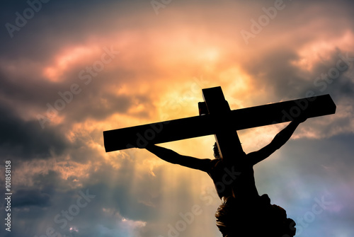 Canvas Print Christian cross with Jesus Christ statue over stormy clouds