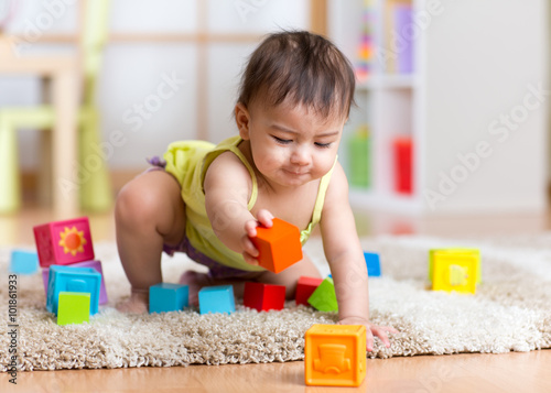 Photo  baby toddler playing  wooden toys at home or nursery