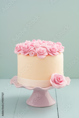 Ivory fondant covered cake with pink sugar roses on cake stand Wallpaper Mural