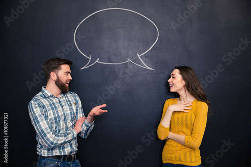 Fotografía  Happy couple talking over chalkboard background with drawn dialogue