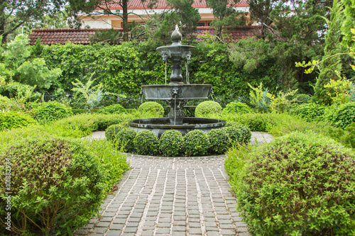 Fotobehang Tuin Nature background. Fountain in english garden design.