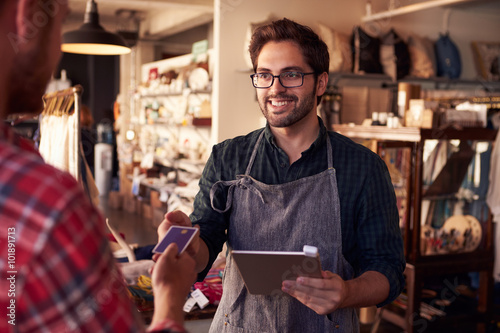Asystent sprzedaży z czytnikiem kart kredytowych na cyfrowym tablecie
