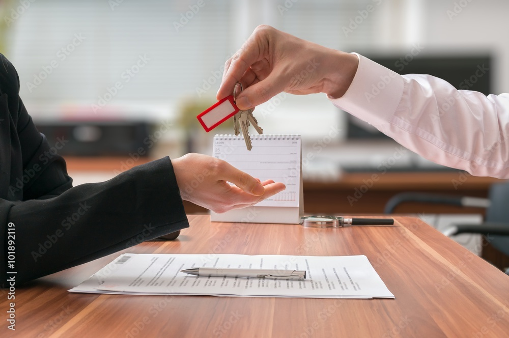Fototapeta Real estate concept. Realtor is passing keys to the client sitting behind desk on blurred background.
