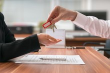 Real Estate Concept. Realtor Is Passing Keys To The Client Sitting Behind Desk On Blurred Background.