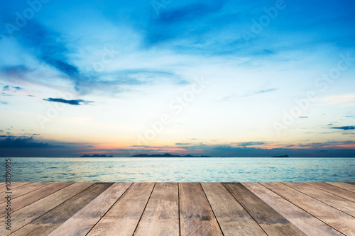Canvas Print Perspective of wood terrace against beautiful seascape at sunset