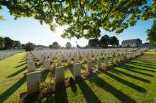 Les Tombes D'un Cimetière Britannique à Ranville, Normandie, France Au Grand Angle En Contre-jour Avec Des Branches D'arbres Au Premier Plan.
