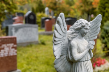 Angel Statue Praying In Front Of Several Tombstones On A Graveya
