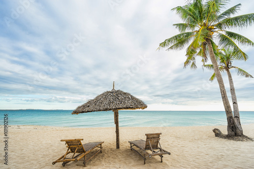 Two Beach Chairs Umbrella And Coconut Palm On The Beautiful Island Travel Concept