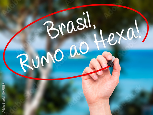 Photo  Man Hand writing Brasil, Rumo ao Hexa! with black marker on visu