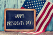 text happy presidents day in a chalkboard and the flag of the US