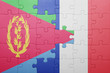 canvas print picture - puzzle with the national flag of eritrea and france