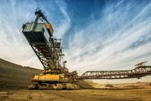 One Side Of Huge Coal Mining Drill Machine Photographed From A Ground With Wide Angle Lens. Dramatic And Colorful Sky In Background.