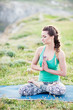Young girl doing yoga fitness exercise outdoor in beautiful mountains landscape.