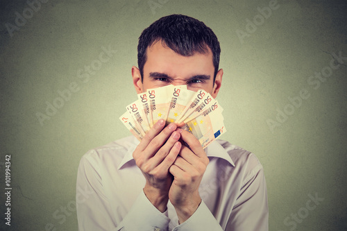 Greedy man with euro banknotes bills isolated on gray wall background Canvas Print