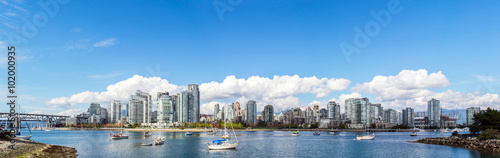 Fotografía panoramic view of the buildings of vancouver city skyline behind a marina during