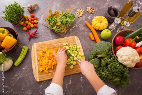 Staande foto Koken Woman chopping vegetables on wooden board