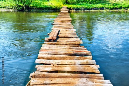 Deurstickers Rivier Old wooden bridge through the river