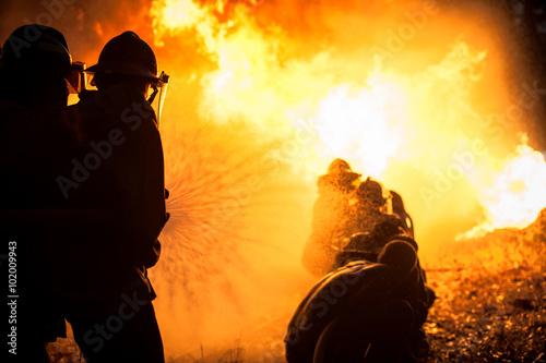 Plakat Sylwetka strażaków walczących z szalejącym ogniem z ogromnymi płomieniami płonącego drewna