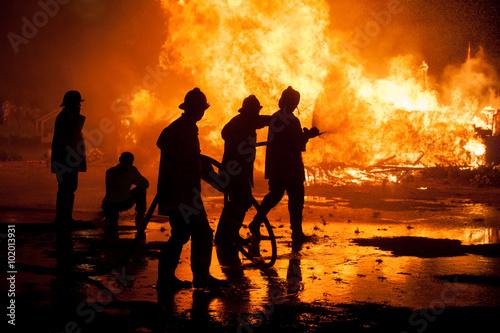 Zdjęcie XXL Sylwetka strażaków walczących z szalejącym ogniem z ogromnymi płomieniami płonącego drewna