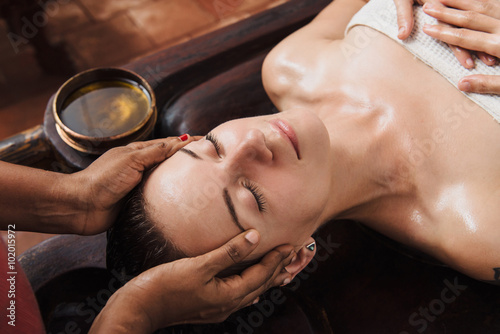 Fototapeta Ayurvedic face massage with oil on the wooden table obraz