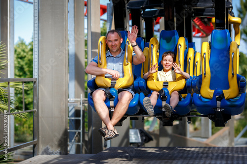 Foto  Father and his little son enjoy the ride at adventure park